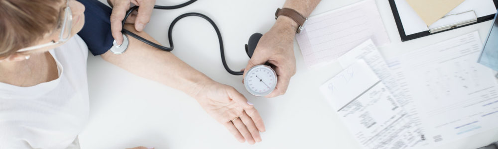 Doctor measuring patient's blood pressure with a specialist equipment