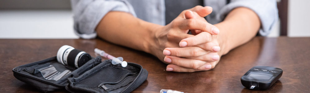 panoramic shot of woman sitting with clenched hands near first aid kit and syringe