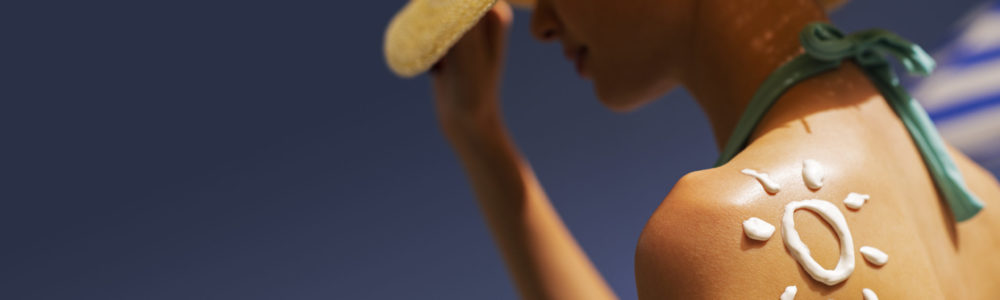 Young beautiful woman tanning at the beach with sunscreen cream on her shoulder, UV protection and skincare concept